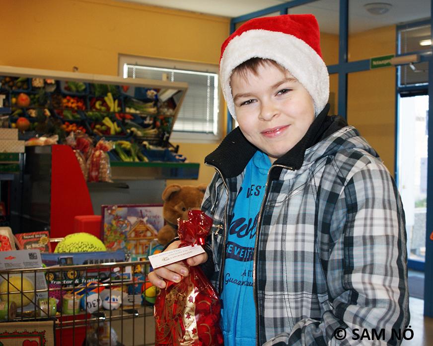 Kind mit Weihnachtsmütze und Geschenkesackerl