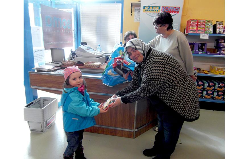 Nazife Menekse, die Marktleiterin, überreicht einem Kind ein Ostersackerl