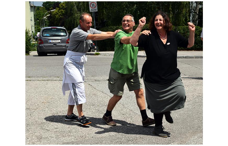 Manu tanzt mit einem Besucher und einem ehrenamtlichen Helfer